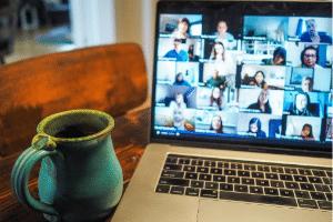 Mug next to laptop showing virtual meeting